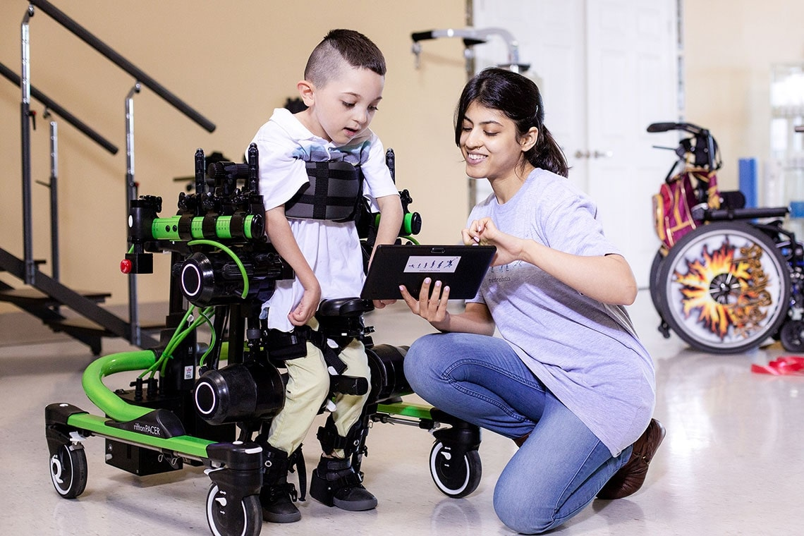Boy with child-sized wearable walking device is guided by researcher.