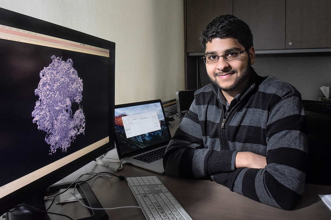 Ali Punjani sits at a computer with drug sequencing on display.